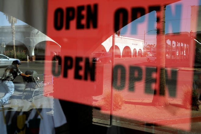 A man passes a clothing shop with open signs in the window June 30 in Calexico, Calif. Records obtained by the Associated Press show governors working closely with business interests as they weighed when and how to reopen their economies during the coronavirus pandemic.