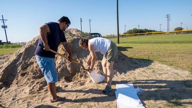 Residents fill sandbags.
