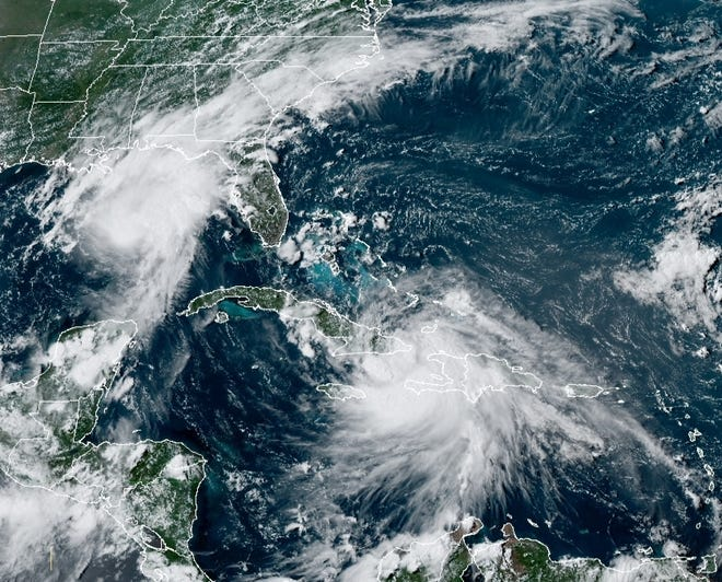 A satellite image shows Hurricane Marco (left) and Tropical Storm Laura on Sunday afternoon.