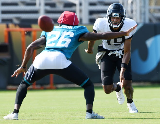 Jaguars receiver Collin Johnson (19) faces off against safety Jarrod Wilson (26) during punting drills. [Bob Self/Florida Times-Union]