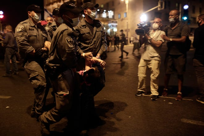 Police carry a protester away as they clear the square outside of Prime Minister Benjamin Netanyahu's residence in Jerusalem late Saturday.