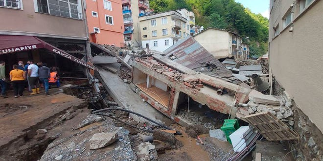 People inspect the destruction after floods caused by heavy rain in the mountain town of Dereli in Giresun province, along Turkey's Black Sea coastline Sunday.