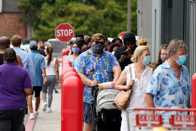 People line up to enter retail chain Costco to buy provisions in New Orleans on Sunday in advance of Hurricane Marco, expected to make landfall on the Southern Louisiana coast.