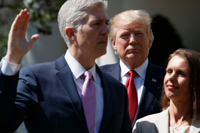 "President Donald Trump watches as Supreme Court Justice Neil Gorsuch, accompanied by his wife Marie Louise, is sworn-in during an April 2017 ceremony in the Rose Garden of the White House in Washington. ""I think the golden egg of Trump's reelection effort is going to be the promises kept, such as getting two Supreme Court Justices in power and keeping America out of foreign wars like Afghanistan and Iraq,"" said Douglas Brinkley, presidential historian at Rice University."