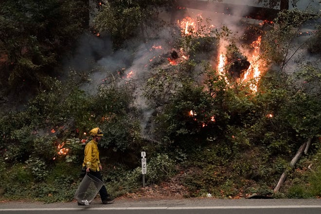 Ben Slaughter, a firefighter for the Boulder Creek Fire Department, walks along Highway 9 while monitoring flames from the CZU August Lightning Complex Fire on Saturday in Boulder Creek, Calif.