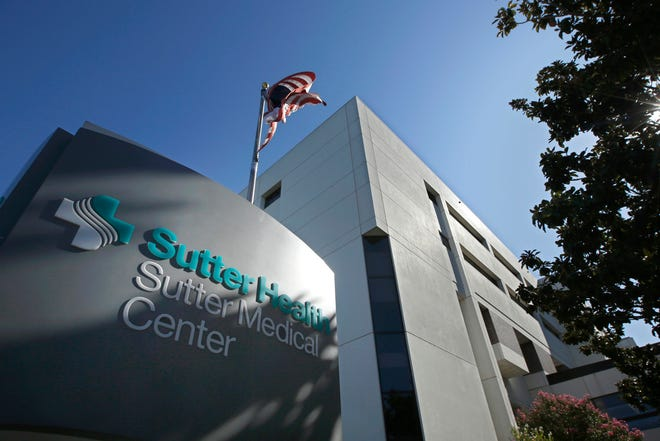 An American flag flutters in the breeze outside of the Sutter Medical Center in Sacramento. California's attorney general wants the power to block hospital mergers that he says would limit competition and drive up prices.