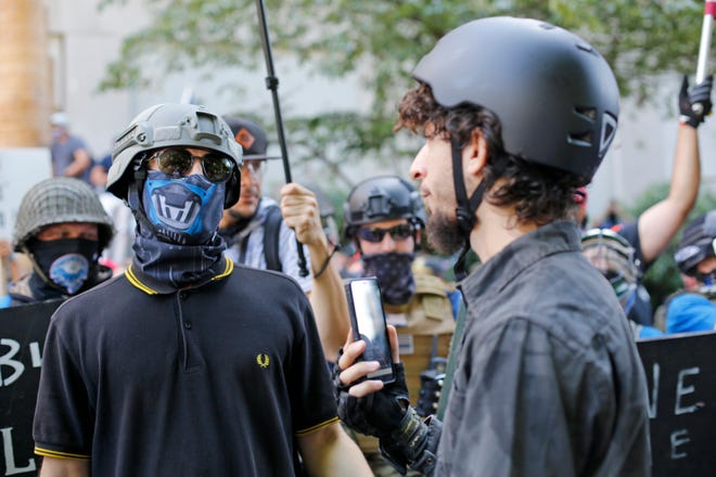 Opposing rallies battle with mace, paint balls and rocks near Justice Center in downtown Portland on Saturday, Aug. 22, 2020. Dueling demonstrations in Portland by right-wing and left-wing protesters have turned violent near a county building that's been the site of numerous recent protests.