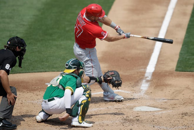 Los Angeles Angels' Mike Trout swings for a two run double off Oakland Athletics' Chris Bassitt in the second inning on Saturday. [AP Photo/Ben Margot]