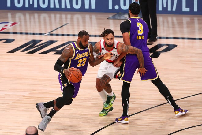 Los Angeles Lakers forward LeBron James (23) drives around Portland Trail Blazers guard Gary Trent Jr. thanks to a screen from Anthony Davis (3) in the first half of Saturday's playoff game in Lake Buena Vista, Fla. (Kim Klement/Pool Photo via AP)