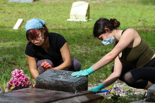 Winnie Blay and Hannah Schenkel scrub a gravestone at Bethlehem Methodist Episcopal Cemetery in Archer on Sunday. Volunteers from the Florida Trust for Historic Preservation, the Florida Public Archaeology Network Central Region and the Bethlehem Methodist Episcopal Cemetery Restoration Organization worked together to clean up the historic, predominantly African American, cemetery.