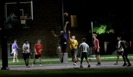 Central Michigan University students play basketball behind the Trout Hall dormitory on a warm night on Saturday August 23, 2020 in Mt. Pleasant, Michigan.