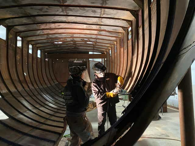 In this image provided by the Harbor Springs Area Historical Society, students from the Industrial Arts Institute make welding repairs to the boat Aha in Onaway.