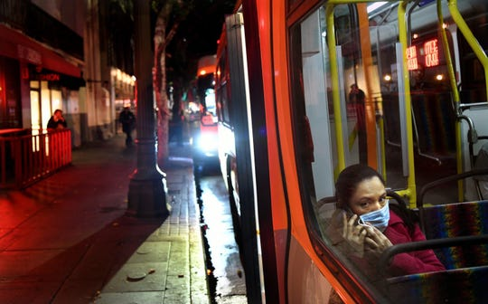 A bus passenger wears a mask during the coronavirus outbreak on March 26, 2020, in downtown Los Angeles.