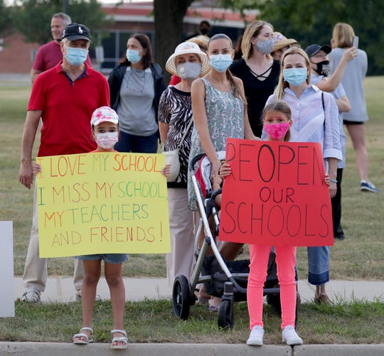 Diana Mejia, left, and Anna Sofiya Iskra, both 8, hold signs while with their mothers, Olga Mejia, second right, and Olena Iskra, far right, during a protest Sunday, Aug. 23, 2020, at Homestead High School of the decision by the Mequon-Thiensville School District to keep schools closed in the fall.