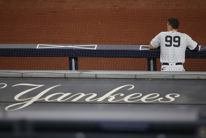 Aug 11, 2020; Bronx, New York, USA; New York Yankees right fielder Aaron Judge (99) watches a game against the Atlanta Braves from the dugout after being removed for a pinch hitter during the sixth inning at Yankee Stadium. Mandatory Credit: Brad Penner-USA TODAY Sports