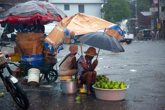 Street vendors protect themselves against the rain from Tropical Storm Laura in Port-au-Prince, Haiti, Sunday, Aug. 23, 2020. ( AP Photo/Dieu Nalio Chery)