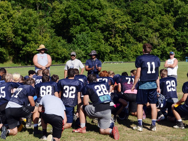 Morgan coach Chase Bowman, middle, talks to his team following practice last week in McConnelsville. The Raiders are one the most experienced teams returning in the Muskingum Valley League this season.