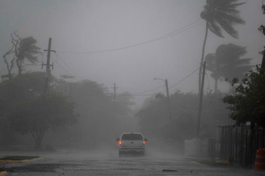 A pickup drives on a road as Tropical Storm Laura hits Guayama, Puerto Rico, on Aug. 22, 2020.
