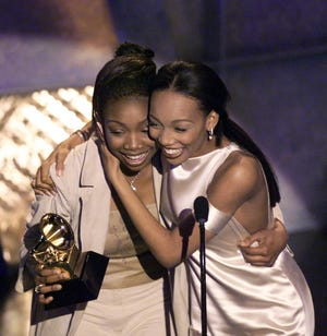 In this file photo from 1999, Brandy and Monica celebrate after winning a Grammy.