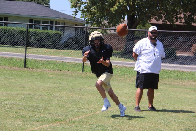 Marietta's Curry Walters hauls in a pass as head coach Alex Doby looks on during a drill.