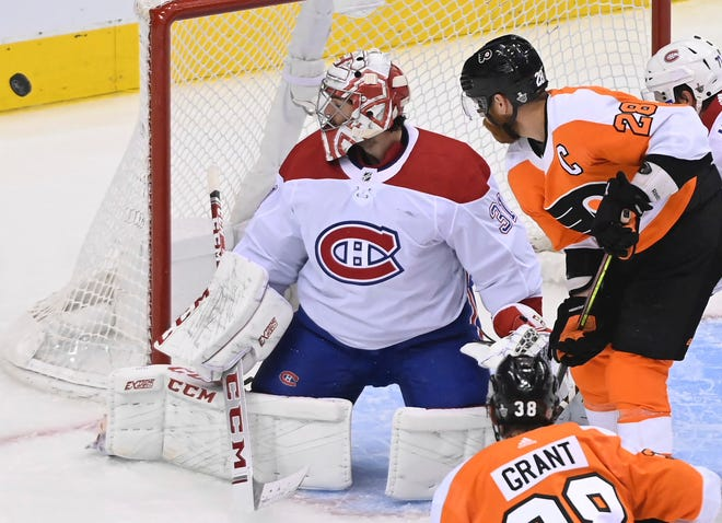 The Flyers' Claude Giroux, 28, and Canadiens goaltender Carey Price watch the puck go wide of the net during Game 5.