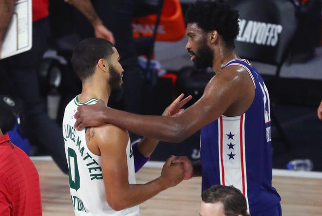 The Sixers' Joel Embiid and the Celtics' Jayson Tatum shake hands after Boston closed out its four-game sweep Sunday.