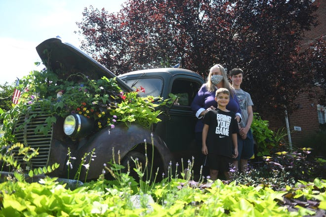 """Denise Fell stands beside a 1938 Ford pick up truck that she and her partner, John Hughes, turned into a community garden in Perkasie.  Fell is grateful that peoplepassing by began leaving notes andgifts for thetruck, including a family of wooden ducks, rabbits, gnome, chicks, birds, plants and painted rocks. """"It was a great way to meet people andit made us feel good so many appreciated it."""""""