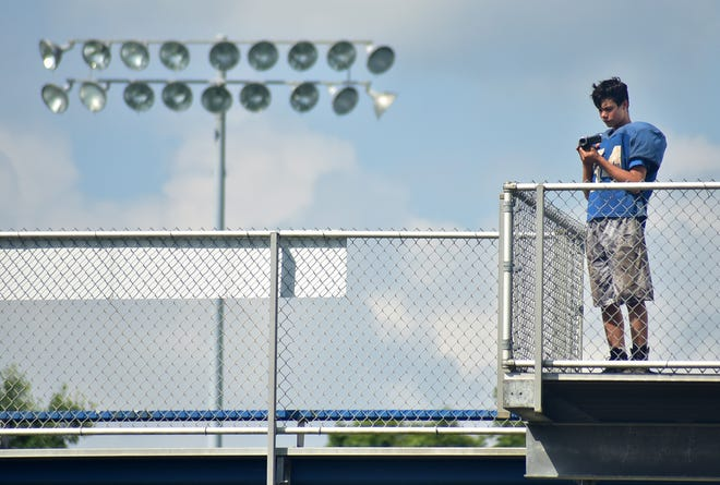 An Ellwood City football player records practice from on top of the bleachers Monday during heat acclimation week. Video streams will be the only way for many fans to watch Ellwood City and the rest of the schools playing Friday night.