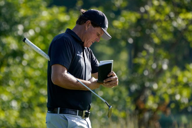 Phil Mickelson refers to his notes as he walks up onto the 14th green during the second round of the Northern Trust at TPC Boston on Friday.