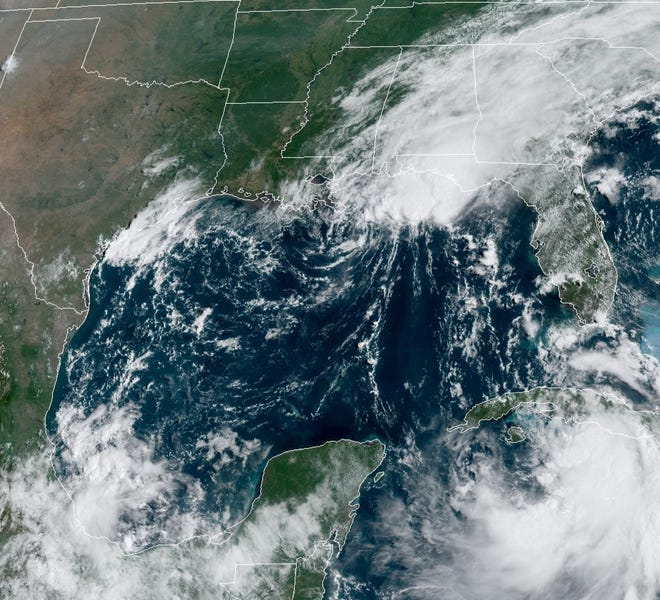 A satellite image shows Tropical Storm Marco as it heads west toward the Louisiana coast Monday morning as Tropical Storm Laura (lower right) churns west in the Caribbean.