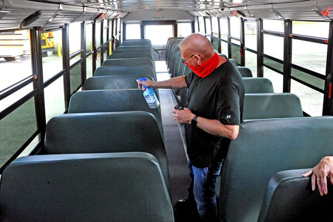 Wooster City Schools transportation supervisor Vic Cole sanitzes the seats in a bus this summer. While most area schools will require students to wear masks on buses, Wooster City Schools also will require students, regardless of vaccination status, to wear masks in school buildings.