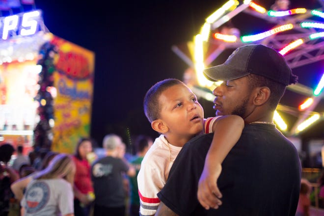Jarvis Webster carries his sleepy son Jameson Webster, 4, through the Maury County Park in Columbia after a long day at the Maury County Fair on Friday, Aug. 30, 2019.