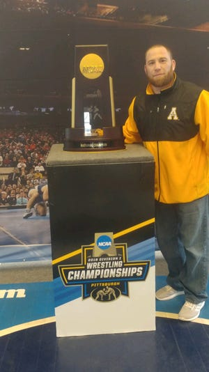 David House poses with the championship trophy at the 2010 NCAA championships.