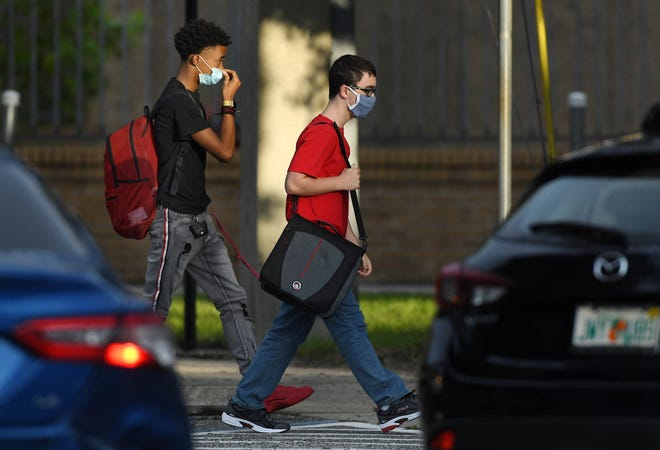Andrew Jackson Senior High School students have their temperature taken before they can enter the building
