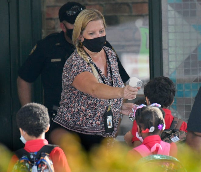 Amanda Kennedy takes student's temperatures at Beauclerc Elementary School on Duval County Public Schools' first day of classes.