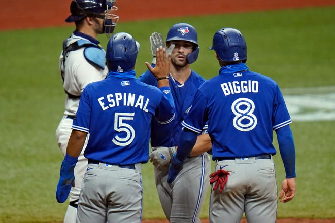 Toronto Blue Jays' Randal Grichuk celebrates his three-run home run off Tampa Bay Rays relief pitcher Aaron Loup with Santiago Espinal (5) and Cavan Biggio (8) during the seventh inning Monday in St. Petersburg.