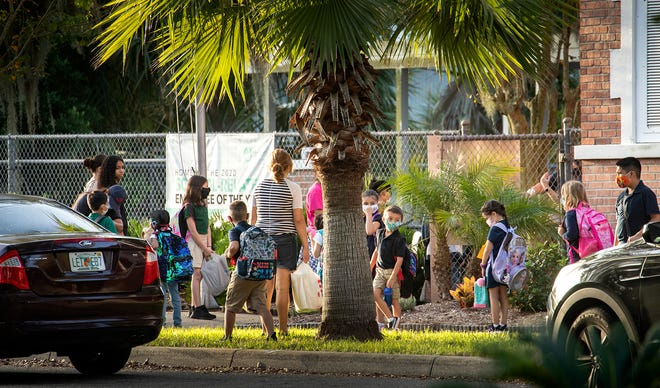 Parents accompany their children to class during the first day of school at Dixieland Elementary in Lakeland.
