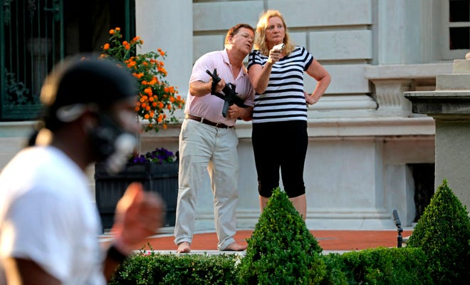 """FILE - In this June 28, 2020 file photo, Mark and Patricia McCloskey emerged from their St. Louis mansion June 28 with guns after protesters walked onto their private street. The couple, who were criminally charged for the incident, will make the case in a recorded message Monday night in their opening night speech of the Republican National Convention that they had a """"God-given right"""" to defend themselves and their property."""