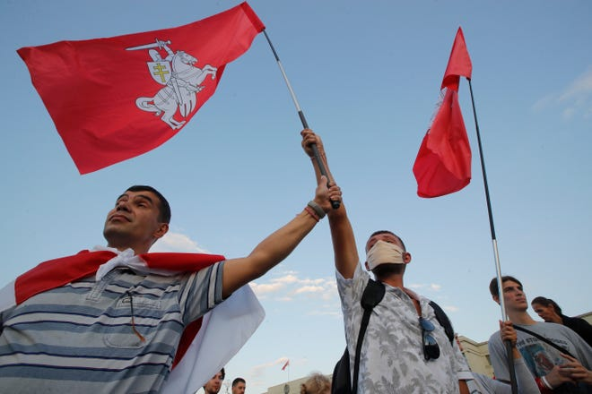 Protesters wave flags with an old Belarusian national emblem during an opposition rally at Independent Square in Minsk, Belarus, on Monday.