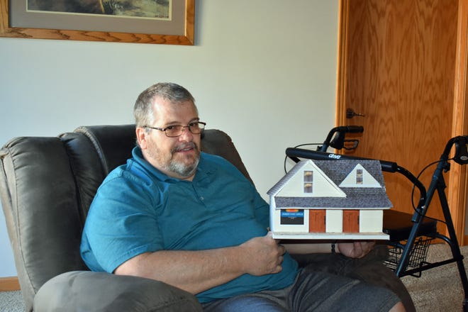 Long-time Zearing resident Tim Adams, now of Eldora, poses with the replica he created of the historic Sunset Post Office, which was once located near Zearing.