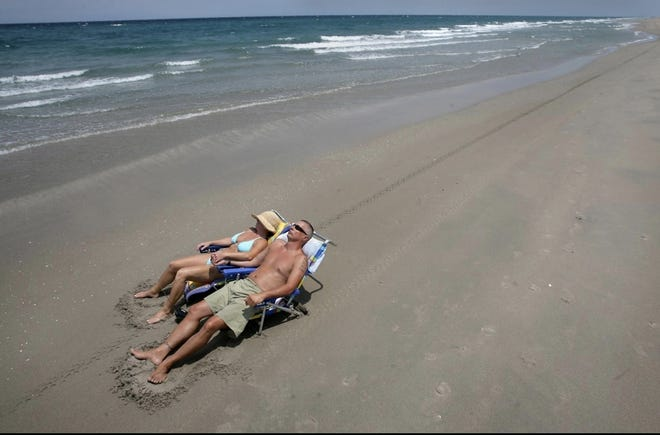 Visitors enjoy the solitude of a nearly empty beach at Spanish River Park in Boca Raton.