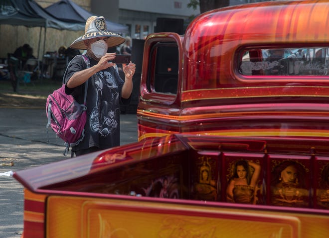 Jose Lopez of San Jose takes a picture of a custom 1936 Ford pickup on display. [CLIFFORD OTO/THE STOCKTON RECORD]