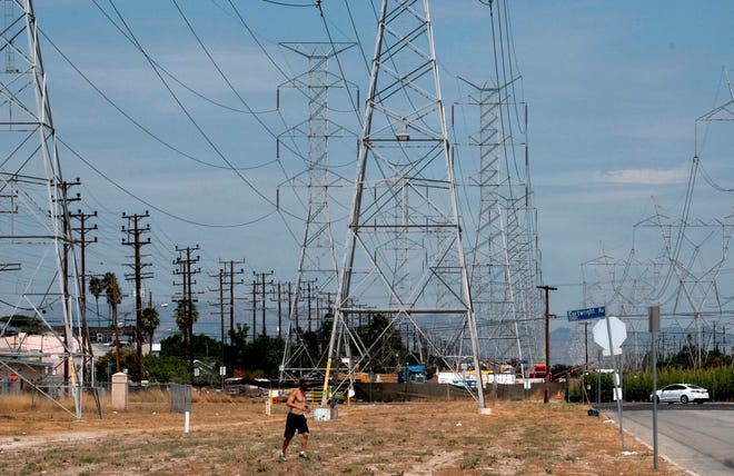 A jogger runs in extreme heat under high tension electrical lines in the North Hollywood section of Los Angeles on Aug. 15, 2020. California' rolling power outages  during the statewide heat wave strained its electrical system.