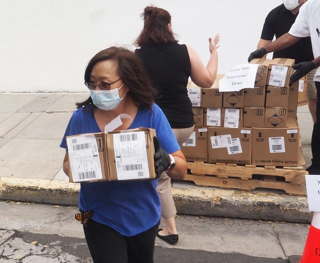 Stockton program manager Florence Low helps load boxes of masks and hand sanitizer. [CALIXTRO ROMIAS/THE STOCKTON RECORD]