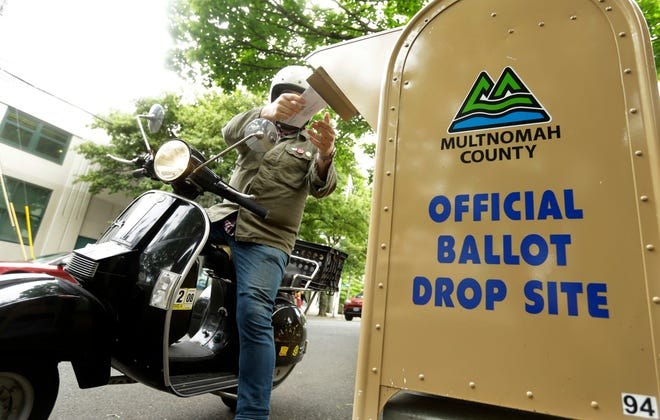 A voter drops off his ballot on May 15, 2018, the day of Oregon's primary election at a drive-by, drop-off station in Portland, Ore. Running an election by mail is a major undertaking, involving the U.S. Postal Service, armies of volunteers and even librarians. But for election officials and voters in Oregon, which pioneered all vote-by-mail in the nation 20 years ago, there's no turning back to the old way of having people cast ballots in person at neighborhood polling places.
