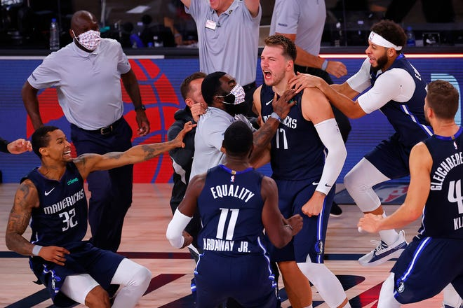 Dallas Mavericks' Luka Doncic (77) celebrates his winning three-point basket with teammates during overtime of Game 4 of an NBA basketball first-round playoff series against the Los Angeles Clippers on Sunday. [Kevin C. Cox/Pool Photo via AP]
