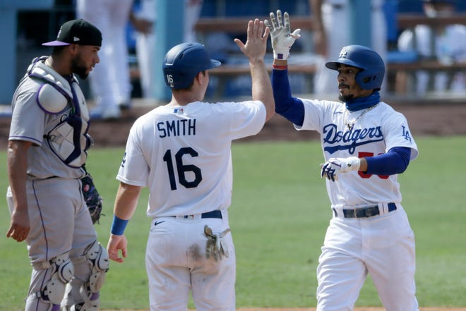 Los Angeles Dodgers' Mookie Betts, right, gets congratulations from Will Smith, after Betts hits a two-run home run, his second home run of the game, with Colorado Rockies catcher Elias Diaz, left, looking away during the eighth inning on Sunday. [AP Photo/Alex Gallardo]