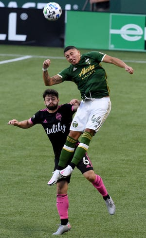 Portland Timbers midfielder Marvin Loria, right, goes up for the ball against Seattle Sounders midfielder Joao Paulo, left, during the first half of an MLS soccer match in Portland. [AP Photo/Steve Dykes]