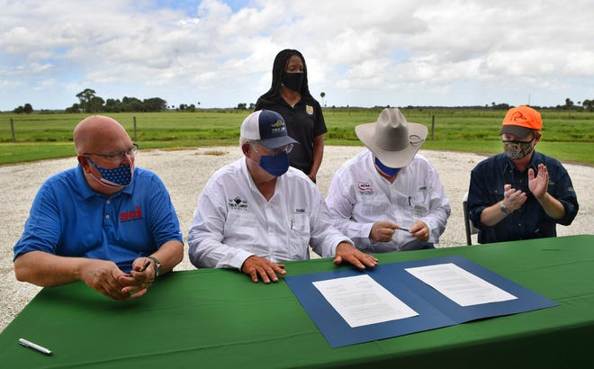 Representatives of four national hunting and ranching organizations met Monday on Blackbeard Ranch in eastern Manatee County to sign a memorandum of understanding. Seated from left: W. Laird Hamberlin, CEO of Safari Club International; Robert Skinner, president of Public Lands Council; Marty Smith, president of the National Cattlemen's Beef Association; and Adam Putnam, CEO of Ducks Unlimited. Auelia Skipwith, director of the U.S. Fish and Wildlife Service, standing, watches.