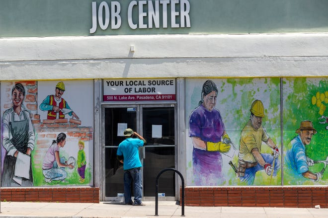 A person looks inside the closed doors of the Pasadena Community Job Center in California. [AP Photo/Damian Dovarganes, File]